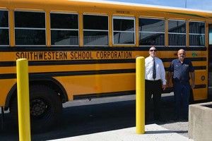 Southwestern Jefferson County School District Superintendent Trevor Jones, left, stands in front of one of the district's new autogas buses.