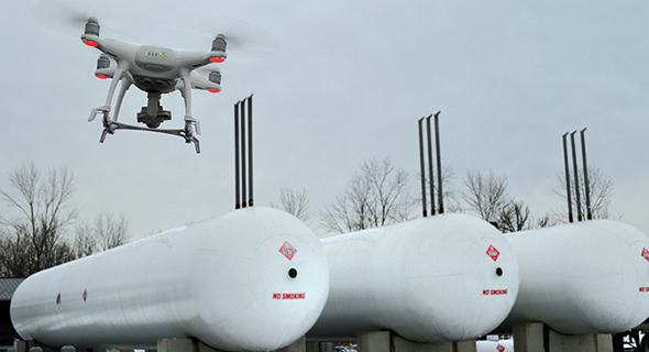 Rosenbaum flies his DJI Phantom III drone over propane tanks at Mulhern Gas.