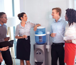 Employee around water cooler stock: Spend some casual time around the water cooler, strike up a personal conversation. Photo iStock.com/Wavebreakmedia