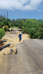 Hawaii Gas' Darin Yoshioka hauls a 20-pound cylinder across a washed-out road in Kauai. Photo courtesy of Hawaii Gas.