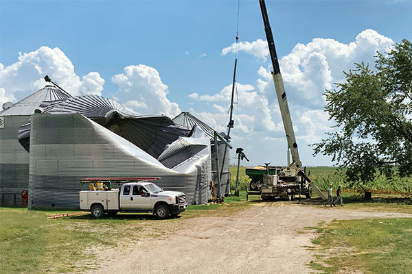 A crane operator prepares to remove grain bins damaged by the derecho near the town of Van Horne in east-central Iowa. Photo by Jay Christie