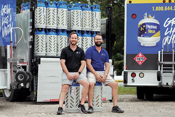 Propane Ninja's Peter Samuelson, left, and Mike Dodd pose in front of the company's composite cylinders. The Florida-based company supplies the cylinders for forklifts, hospitality and retail propane exchange. Photo courtesy of Trent Bamberry