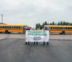 From left: Lance Gerry, school mechanic, Harrisburg, S.D.; Russ Nelson, school mechanic, Lennox, S.D.; and Eric Kracke, CHS certified energy specialist, are advocates of the transition to propane-fueled school buses. Propane buses in front of the 12,000-gallon bullet at the Harrisburg fill station. (Photo: CHS, Inc.)